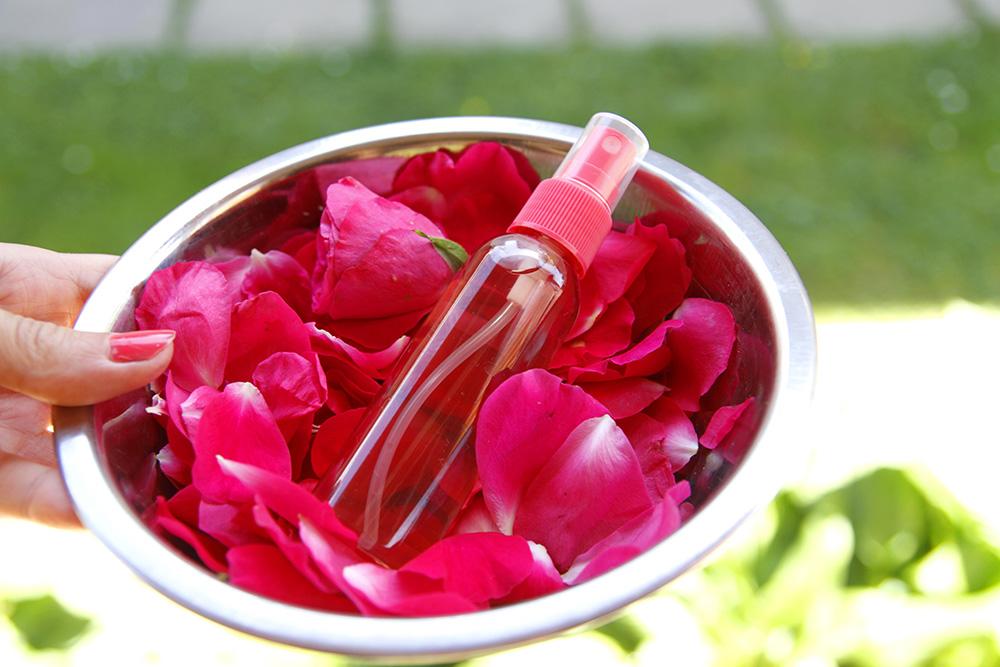 Ružová voda vo flakóne v miske s ružovými lupeňmi
