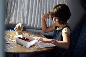 Dievčatko sediace za stolom, ovocné kože v nádobke na stole