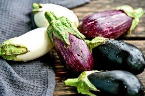 Biele, fialové a tmavé baklažány na stole