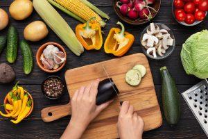 Zelenina na kuchynskej linke, ruky krájajú baklažán