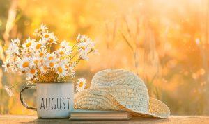 Letný deň, slamený klobúk a plechový hrnček s kvetmi na stole