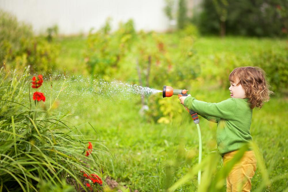 Dieťa polievajúce záhradu