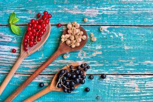 Čierne, červené a biele ríbezle na vareškách na modrom stole