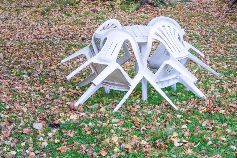 Plastový stôl so stoličkami v záhrade, jeseň