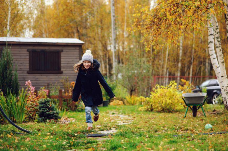 Dievčatko utekajúce jesennou záhradou