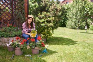 Bruneta v záhrade s muškátmi v kvetináčoch