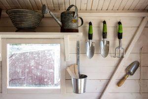 Interiér záhradného domčeka, okno s poličkou, náradie na stene