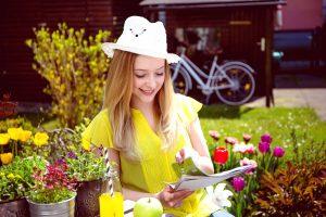 žena číta časopis v záhrade