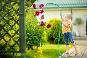 Dievčatko polieva kvety v záhrade