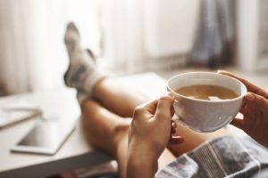 Čaj v bielej šálke, nohy na stole