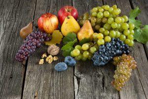 Hrozno, jablká, slivky a hrušky na drevenom podklade
