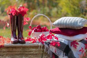 Jesenné zátišie v záhrade, červené gumáky, lístie, vankúše a deky