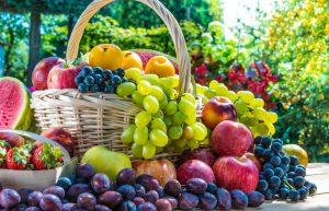 Hrozno, slivky, jablká a marhule v košíku